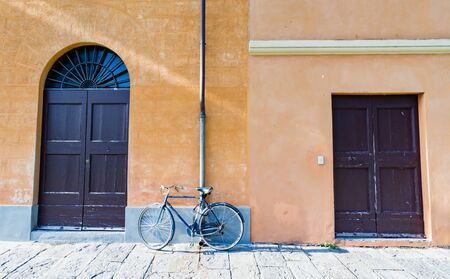 leaning against: A bicycle leaning against the wall between two doors