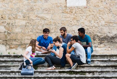 church group: SAN GIMIGNANO, ITALY - JUNE 11, 2016 - A multi-ethnic group of guys having fun chatting on the stairs of a church in a square in San Gimignano in Tuscany