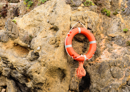 lifebelt: A lifebuoy or lifebelt hanging on a rock