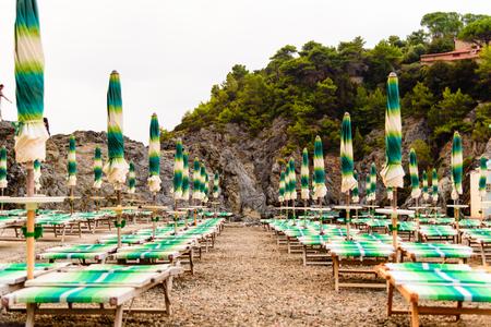 soltería: Filas de paraguas cerrados y tumbonas en la playa vacía.