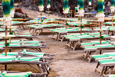 not open: Rows of closed umbrellas and deckchairs on the empty beach.