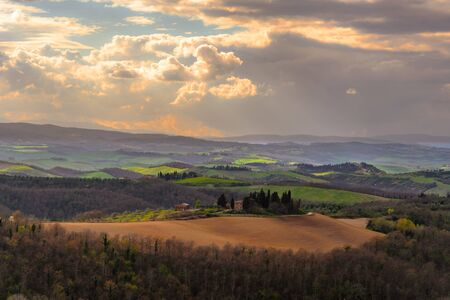 SIENA, ITALY - MARCH 26, 2017 - View of the countryside near Siena, Italy with a house surronded by cypress trees.