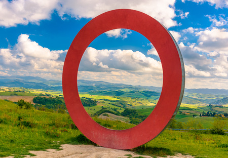 VOLTERRA, ITALY - APRIL 22, 2017 - View of the tuscan countryside with a sculpture along the road for Volterra.