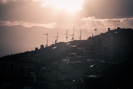 夕日時のトスカーナでのヴォルテッラ有名な市の建物の屋根にテレビ アンテナ