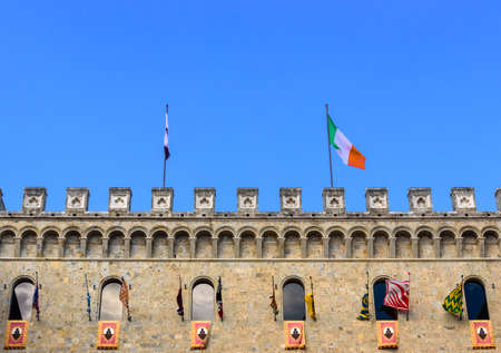SIENA, ITALY - JULY 2, 2017 - The flags participating in the Palio di Siena exhibited in the palace of Rocca Salimbeni headquarters of the bank Monte dei Paschi di Siena.