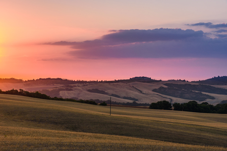 val: PIENZA, ITALY - JULY 23, 2017 - View of the countryside of ValdOrcia Natural Area in Tuscany during summer at sunset.