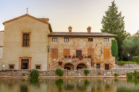 a bathing place: BAGNO VIGNONI, ITALY - JULY 23, 2017 - View of the church and the medieval thermal baths in Bagno Vignoni a small village in ValdOrcia. Editorial