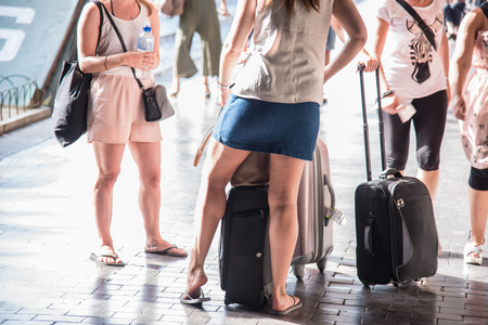Girls wait for a train with suitcases along the platform of a station