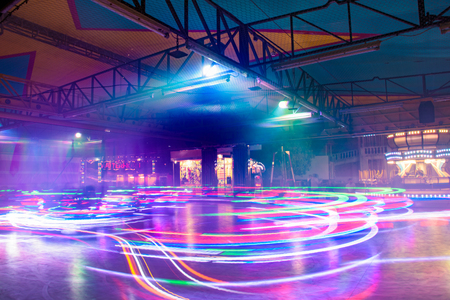 SIENA, ITALY - MAY 19, 2017 - The bright strips of dodgem cars in an amusement park. Long exposition.