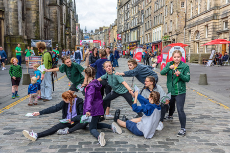 EDINBURGH, UNITED KINGDOM - AUGUST 16, 2017 - A group of young girls advertises a theatrical performance along the Royal Mile of Edinburgh during the 70th anniversary of the Fringe Festival.