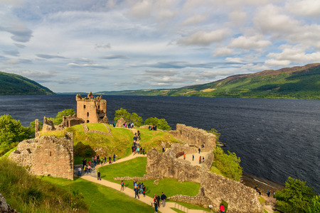 INVERNESS, SCOTLAND - AUGUST 10, 2017 - View of Urquhart Castle in Scotland with a row of visitors exploring castle ruins. Stock Photo