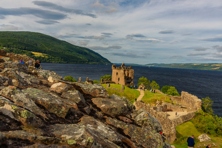 INVERNESS, SCOTLAND - AUGUST 10, 2017 - View of Urquhart Castle in Scotland with a row of visitors exploring castle ruins. 版權商用圖片
