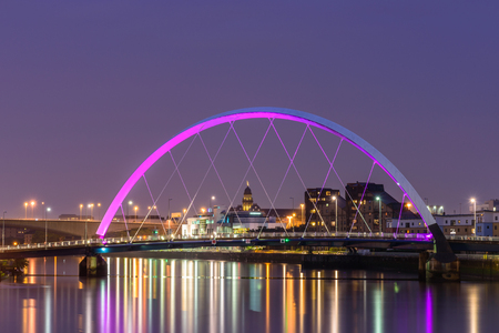 Night lights and the Clyde Arc Bridge at Glasgow City in Scotland over river.