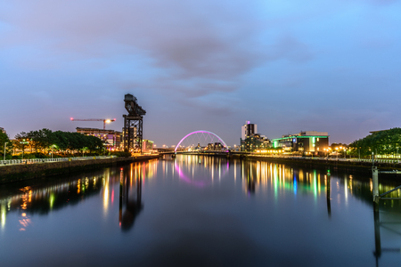 Night lights and the iconic Clyde Arc Bridge at Glasgow City in Scotland over river.