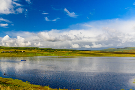 The wonderful nature of the Isle of Skye with a single boat in the middle of a river