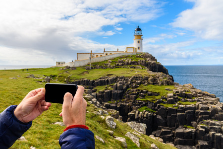 A man photographs the Neist point lighthouse in the Isle of Skye in Scotland with his smartphone.