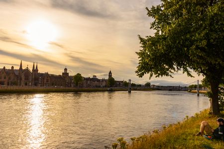 ness river: INVERNESS, SCOTLAND - AUGUST 11, 2017 - A boy relaxes on the banks of the Inverness River during sunset. Editorial