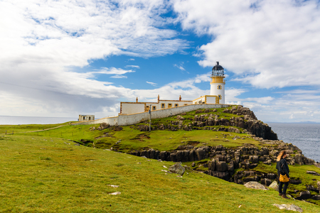 A tourist admires Neist Point lighthouse in the Isle of Skye in Scotland, UK