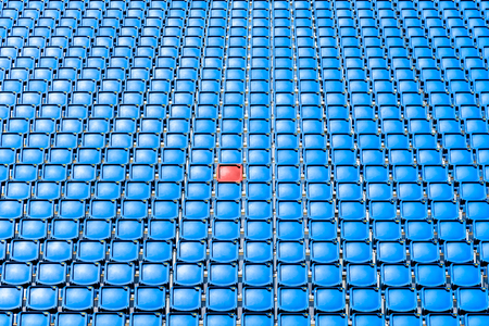 A red seat in the middle of blue seats