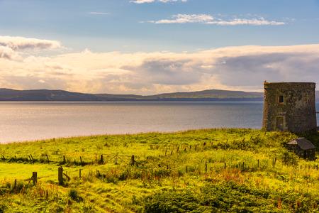 Vue panoramique sur l'océan et la nature luxuriante de l'île de Skye, en Écosse en été avec un bâtiment abandonné en premier plan. Banque d'images - 90454497
