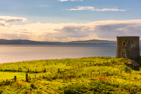 Scenic view of the ocean and the lush nature of the Isle of Skye, Scotland in summer with an abandoned building in foreground.