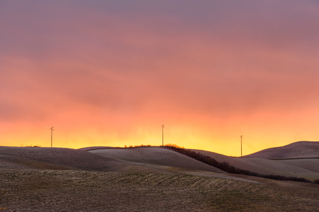 Light poles against sunset in tuscan countryside