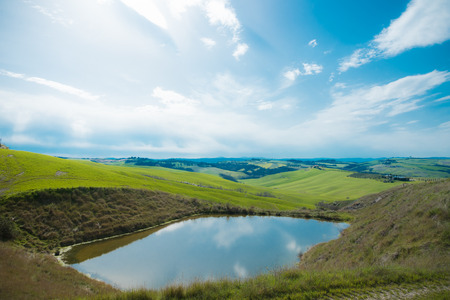 Country landscape with soft green hills and water during springtime.