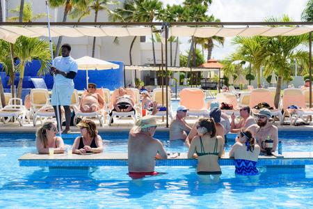 Oranjestad, Aruba - January 15, 2018: People chat and have fun in a swimming pool in a resort of Aruba Editorial