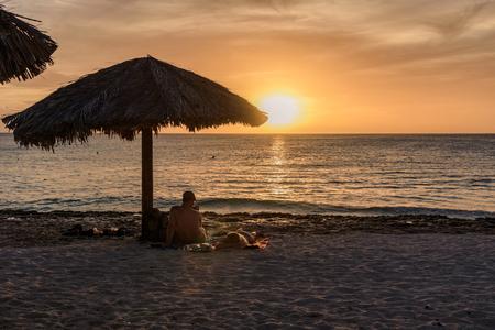 Oranjestad, Aruba - January 13, 2018: Tourist watch the scenic sunset in the beautiful beach of Boca Catalina in Aruba. Editorial