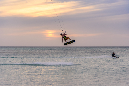 Oranjestad, Aruba - January 16, 2018:A sporty man does acrobatics while practicing kitesurfing at sunset in Aruba.