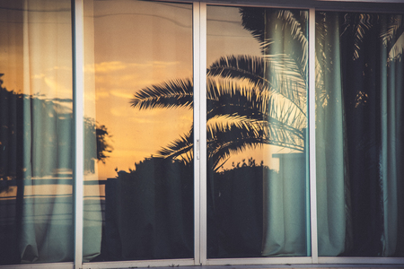 A sunset at the caribbean reflected on a window glass Stock Photo