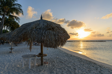 Tropical nature at sunset with white sand beach, parasol and palm tree. Stock Photo