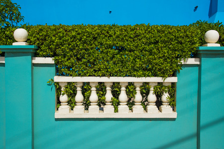 A white fence with a pastel-colored water-green wall and a hedge Stock Photo
