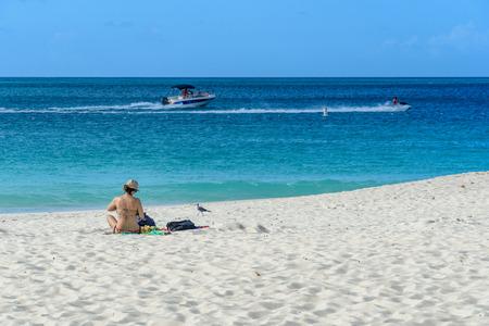 Oranjestad, Aruba - January 13, 2018: A woman relax in the white sand of the idyllic Eagle Beach in Aruba.