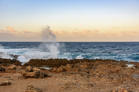 The force of the sea in Aruba with waves break on the rocks, near the Natural Bridge. Stock Photo