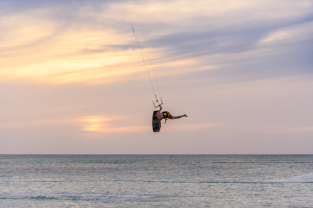 Oranjestad, Aruba - January 16, 2018:A sporty man does acrobatics while practicing kitesurfing at sunset in Aruba. Stock Photo - 108335961