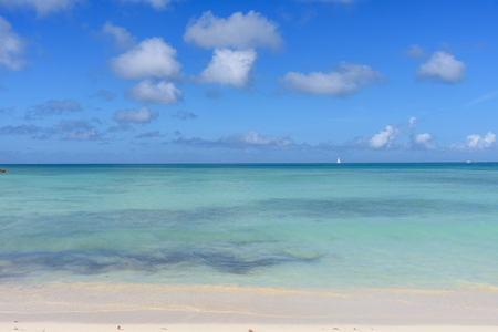 Tropical background with wahite sand beach, turquoise water and blue sky.