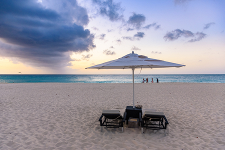 Sunbeds and a parasol at sunset in a tropical caribbean beach