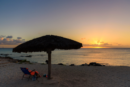 Sun bed and umbrella at sunset. Caribbean seascape
