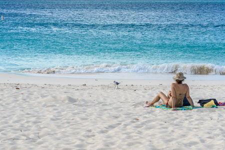 Oranjestad, Aruba - January 13, 2018: A woman relax in the white sand of the idyllic Eagle Beach in Aruba. Stock Photo - 108349447