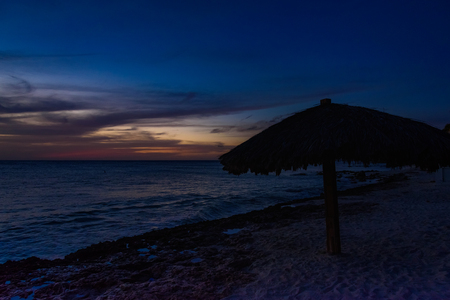 Last light in Aruba with a parasol in foreground Stock Photo - 108336122