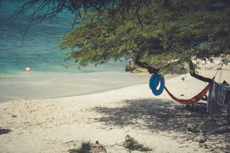 View of an idyllic caribbean beach with an hammock and a life ring Stock Photo - 108336123