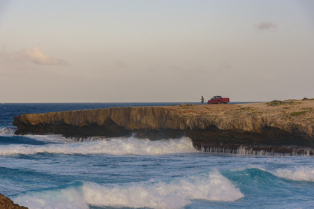 An adult man fishing near a cliff in Aruba with his car.