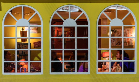 Oranjestad, Aruba - January 13, 2018: The window of a restaurant in the colorful center of Oranjestad with some people doing dinner Stock Photo - 108349450