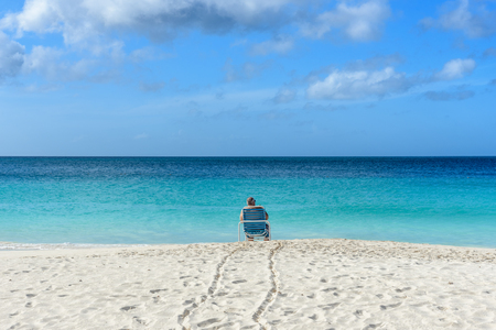 A man relax on a chair in the idyllic shore of the Eagle Beach in Aruba