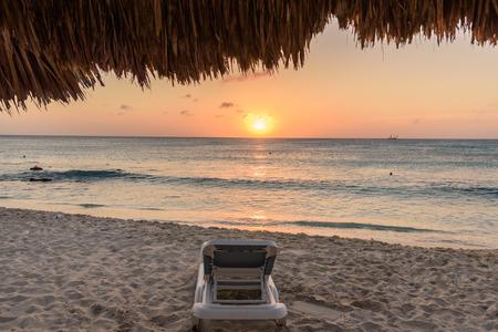 Empty sun bed on the idyllic caribbean shore of Arashi Beach in Aruba at sunset