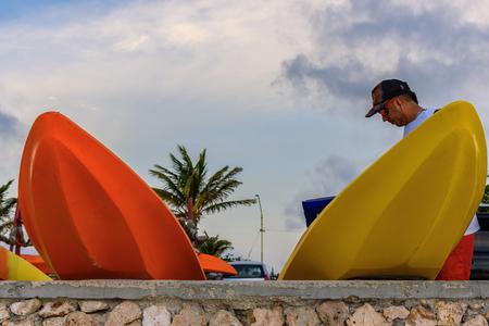Oranjestad, Aruba - January 11, 2018: A man puts on a wall some surfboards for tourists in the beautiful Arashi Beach in Aruba.