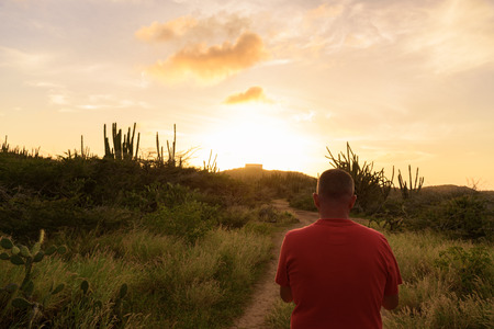 An adult man in a road at sunset near the Alto Vista Chapel in Aruba Stock Photo