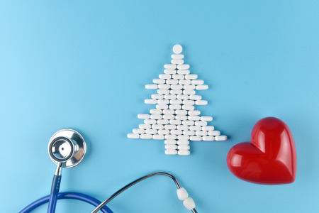 Medicine pills shape of christmas tree and others equipment of doctor on blue background. Concept christmas and new year.