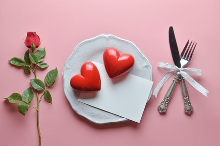 Red couple heart and greeting card on white dish, with fork and knife in ribbon, Rose, On pink background, Concept of Valentine's Day, Romance, Love, dinner, Special day